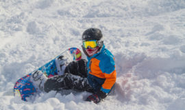 Snowboarder Sitting In Powder Sunny Goggles