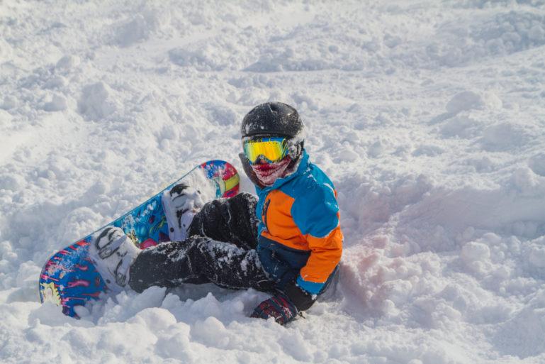 Snowboarder Sitting In Powder Sunny Goggles
